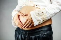 Femme enceinte créant la forme de coeur sur le ventre Images libres de droits