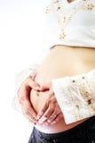 Femme enceinte créant la forme de coeur sur le ventre Photographie stock libre de droits