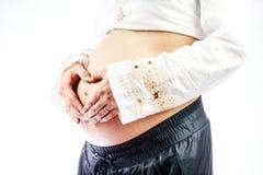 Femme enceinte créant la forme de coeur sur le ventre Photo libre de droits