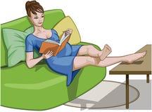 Femme enceinte décontractée lisant un livre sur un divan Photographie stock