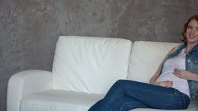 Femme enceinte détendant à la maison le regard très heureux banque de vidéos