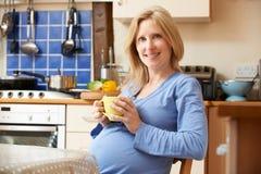 Femme enceinte détendant dans la cuisine avec la tasse de thé photos libres de droits