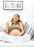 Femme enceinte détendant sur le divan avec la cuvette de thé Photo stock