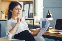 Femme enceinte d'affaires travaillant à la maternité de bureau se reposant tenant le rapport photos libres de droits