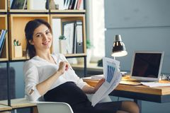 Femme enceinte d'affaires travaillant à la maternité de bureau se reposant tenant le rapport de projet photos stock