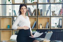 Femme enceinte d'affaires travaillant à la maternité de bureau se tenant regardante le sourire d'appareil-photo photographie stock libre de droits