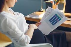 Femme enceinte d'affaires travaillant au rapport se reposant de lecture de maternité de bureau images stock