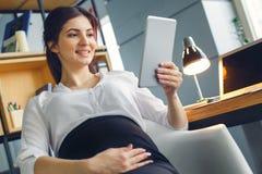 Femme enceinte d'affaires travaillant aux vidéos de observation se reposantes de maternité de bureau sur le comprimé numérique photographie stock libre de droits