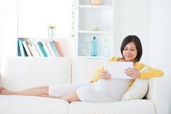 Femme enceinte d'Asiatique à l'aide de l'ordinateur de tablette photos libres de droits