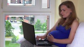 Femme enceinte d'indépendant travaillant avec l'ordinateur portable se reposant par la fenêtre à la maison clips vidéos