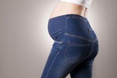 Femme enceinte dans des blues-jean pour les femmes enceintes sur le fond gris Photos libres de droits