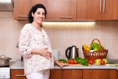 Femme enceinte dans l'intérieur de cuisine avec des fruits frais et des légumes, concept sain de nourriture Images libres de droits