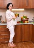 Femme enceinte dans l'intérieur de cuisine avec des fruits frais et des légumes, concept sain de nourriture Photographie stock libre de droits