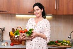 Femme enceinte dans l'intérieur de cuisine avec des fruits frais et des légumes, concept sain de nourriture Photos libres de droits