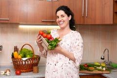 Femme enceinte dans l'intérieur de cuisine avec des fruits frais et des légumes, concept sain de nourriture Photo libre de droits