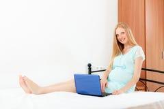 Femme enceinte dans la chemise de nuit avec l'ordinateur portable Photos libres de droits