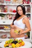 Femme enceinte dans la cuisine avec un plat de salade de fruits Photo stock