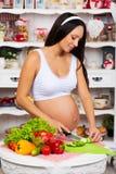 Femme enceinte dans la cuisine préparant une salade végétale Nutritif sain Image stock