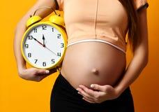 Femme enceinte dans la grande montre d'horloge de prise supérieure de chemise souriant sur le jaune Images libres de droits