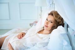 Femme enceinte dans le chemisier blanc se trouvant sur le lit Pièce bleue Image libre de droits