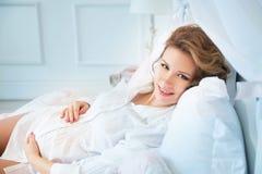 Femme enceinte dans le chemisier blanc se trouvant sur le lit Sourire Photographie stock libre de droits