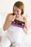 Femme enceinte dans le sourire de chocolat de consommation de bâti Photos stock
