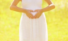 Femme enceinte de concept ensoleillé montrant des mains au coeur de forme Photos stock