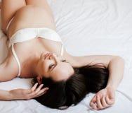 Femme enceinte de jeune jolie brune s'étendant dans le lit sur l'intérieur blanc de merdes, tendresse de concept de personnes de  Photographie stock libre de droits