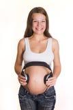 Femme enceinte de jeunes avec des écouteurs sur le ventre Photographie stock