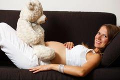 Femme enceinte de jeunes avec l'ours de nounours Photographie stock libre de droits