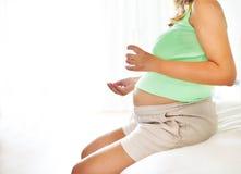 Femme enceinte de jeunes avec la médecine et verre de l'eau images libres de droits