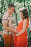 Femme enceinte de jeunes avec son mari tenant des mains sur son ventre Photos libres de droits