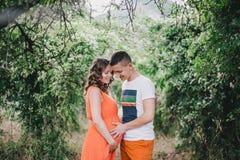 Femme enceinte de jeunes avec son mari tenant des mains sur son ventre Photographie stock