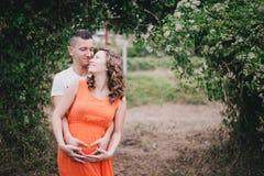 Femme enceinte de jeunes avec son mari tenant des mains sur son ventre Photo libre de droits