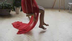 Femme enceinte de jeunes balançant sur une oscillation en bois Une jeune fille dans une longue robe rouge sur une oscillation dan clips vidéos