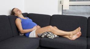 Femme enceinte de jeunes détendant sur le sofa Image libre de droits