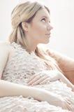 Femme enceinte de jeunes dans la séance rose de robe Image stock