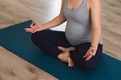 Femme enceinte de jeunes dans un studio de yoga méditant sur un tapis photo stock