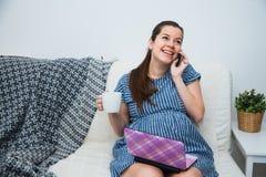 Femme enceinte de jeunes faisant des emplettes en ligne avec la carte de crédit d'ordinateur portable et le smartphone Image stock