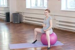 Femme enceinte de jeunes faisant des exercices gymnastiques photographie stock libre de droits
