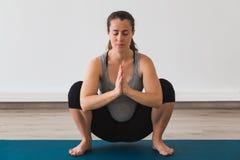 Femme enceinte de jeunes faisant la pose prénatale de yoga avec des mains de namaste photographie stock
