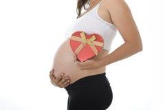Femme enceinte de jeunes jugeant le grand ventre boîte en forme de coeur de coeur disponible et rouge d'amour Images libres de droits