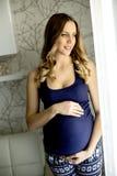 Femme enceinte de jeunes par la fenêtre photo stock