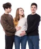 Femme enceinte de jeunes posant avec le jeune homme deux Photo stock