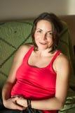 Femme enceinte de jeunes posant sur le divan Image libre de droits