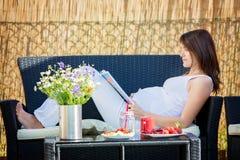 Femme enceinte de jeunes, prenant le petit déjeuner sain dans le jardin Image stock