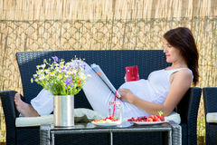 Femme enceinte de jeunes, prenant le petit déjeuner sain dans le jardin Photo libre de droits