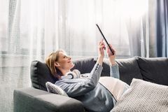 Femme enceinte de jeunes reposant et à l'aide du comprimé sur le sofa gris image libre de droits