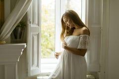 Femme enceinte de jeunes se tenant prêt la fenêtre photographie stock