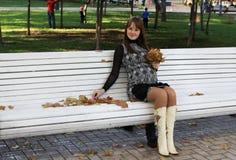 Femme enceinte de jeunes sur le banc avec des lames d'automne photos libres de droits